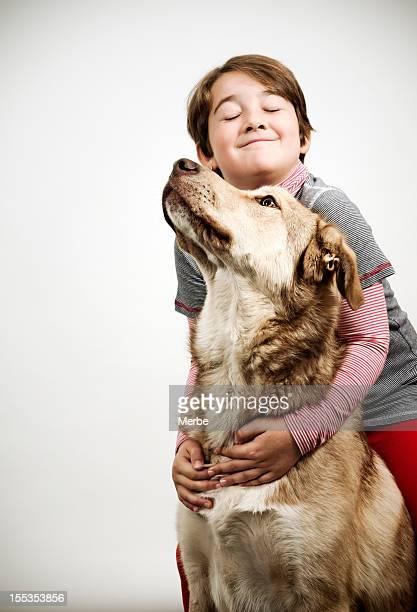 A happy boy hugging a large dog