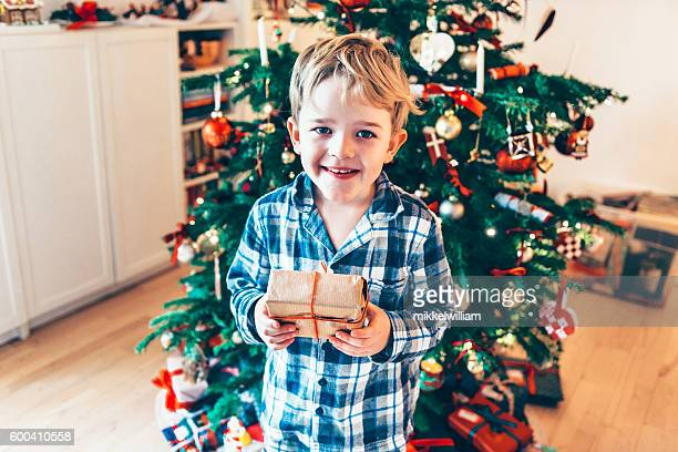 Happy boy in pajamas gets present christmas morning