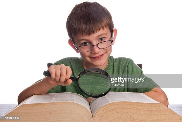 Happy Boy Looking at Book with Magnifying Glass