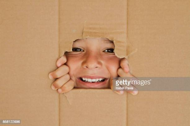 Happy Boy looking through a hole on cardboard