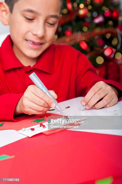 Happy boy making christmas cards