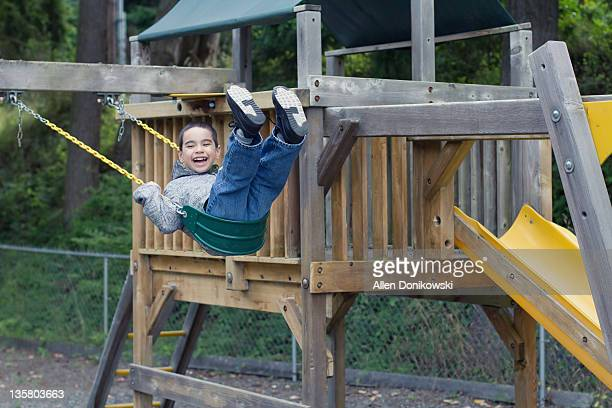 Happy boy on swing at playground