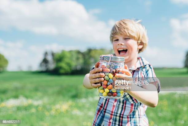 Happy boy outdoors holding glass with jelly beans