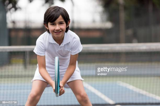 Happy boy playing tennis and looking at the camera