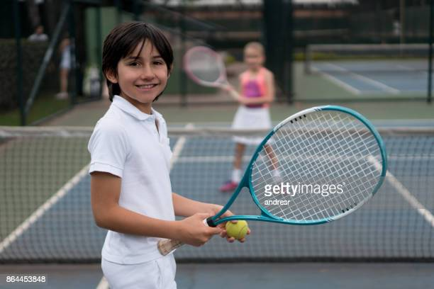 Happy boy playing tennis outdoors with a friend