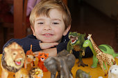 Happy boy playing with animal toys