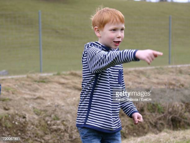 Happy Boy Pointing While Standing On Grassy Field Against Fence