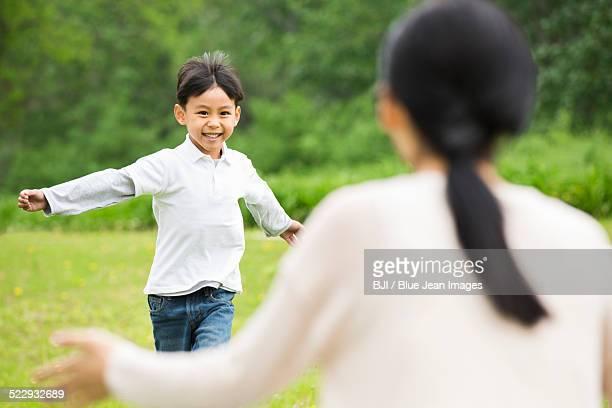 Happy boy running to hug his mother