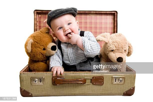 Glückliche junge sitzt in retro-Koffer mit seinem teddy Bären