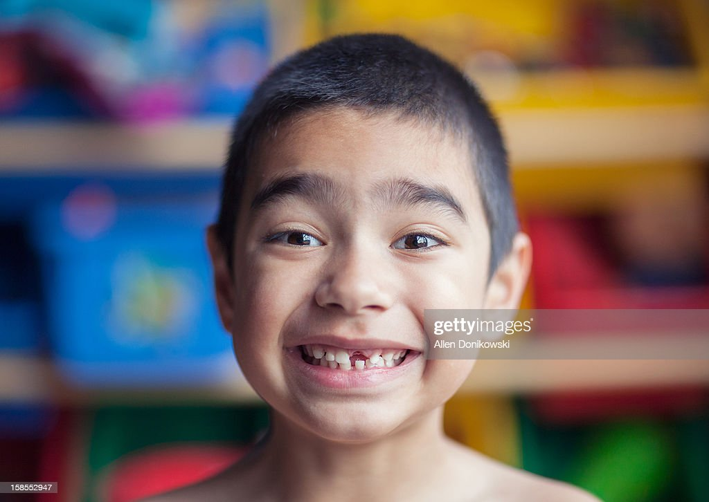 happy boy smiling with lost front tooth at home : Stock Photo