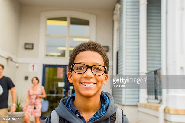 Happy boy standing in front of school