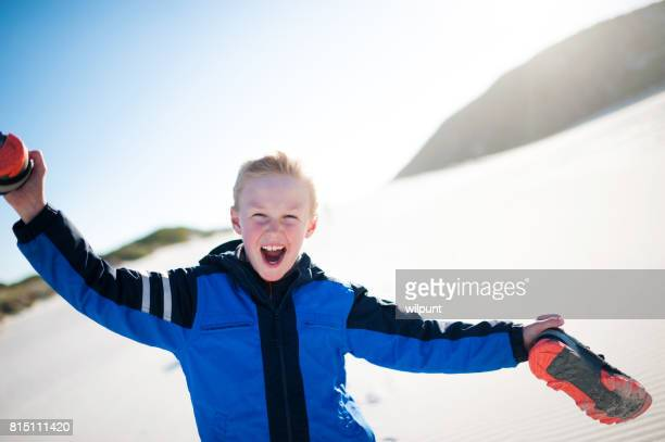 Happy boy with arms raised and shoes in hands