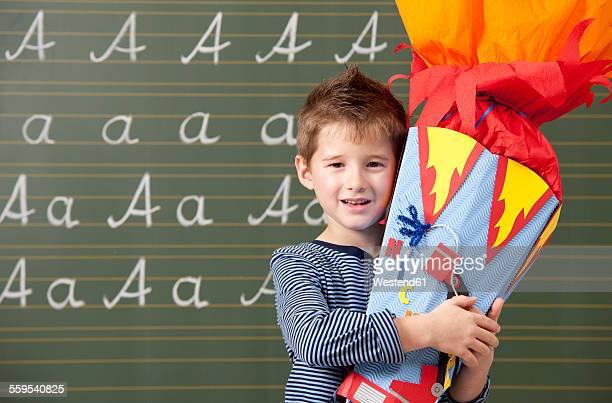 Happy boy with school cone at blackboard
