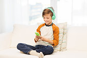 leisure, children, technology and people concept - smiling boy with smartphone and headphones listening to music or playing game at home