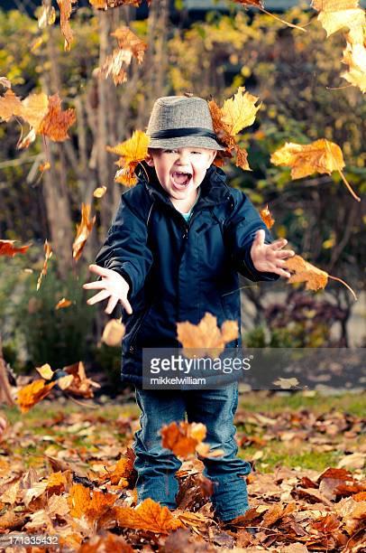 Niños felices exclusivo de las hojas en el aire
