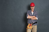 Successful bricklayer with red helmet and equipment tool kit on waist standing against grey wall. Portrait of happy manual worker isolated over grey background. Satisfied mature craftsman with copy sp