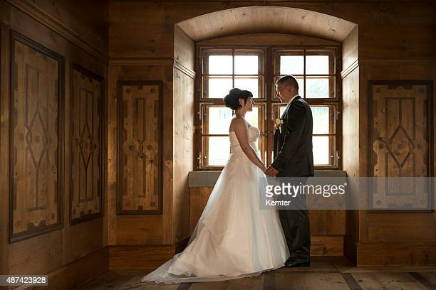 happy bridal couple standing at a window