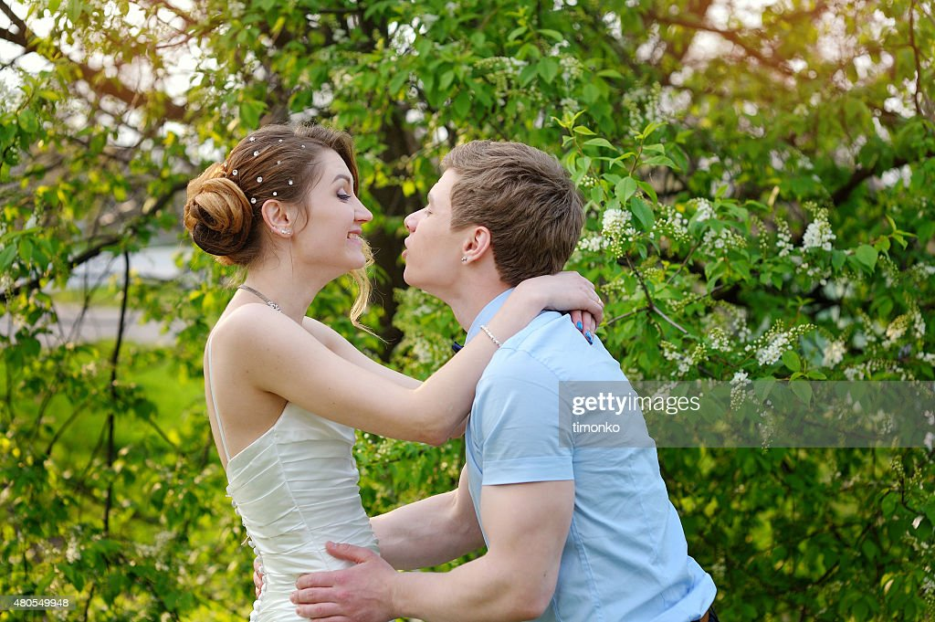 Feliz novia y el novio beso de boda en park : Foto de stock
