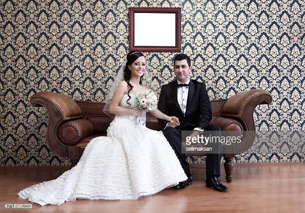 Happy bride and groom sitting on sofa