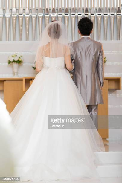 チャペルで聖職者の前に幸せな新郎新婦立って