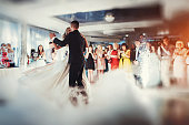 Happy bride and groom and their first dance, wedding in the elegant restaurant with a wonderful light