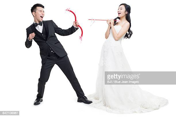 Happy bride and groom with bow and arrow