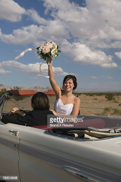 Happy bride driving away in convertible with groom