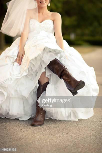 Glückliche Braut im Hochzeitskleid und Cowboy-Stiefel