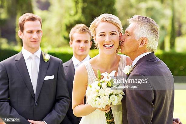 Happy Bride Looking Away While Father Kissing Her On Cheek