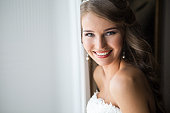 Beautiful smiling Bride wedding Portrait with wedding hairstyle, Wedding dress. Wedding decoration. soft selective focus. gorgeous young woman in hotel room