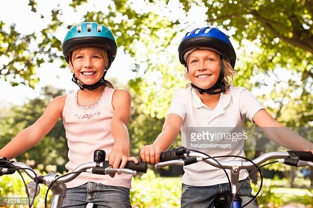 Feliz irmão e irmã no parque de Ciclismo