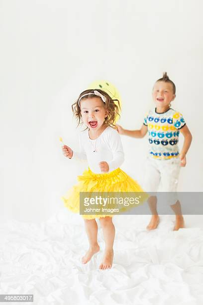 Happy brother and sister jumping on bed