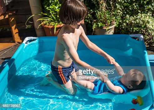 Happy brothers playing in inflatable pool on summer day