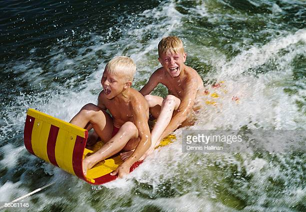 Happy brothers riding water sled