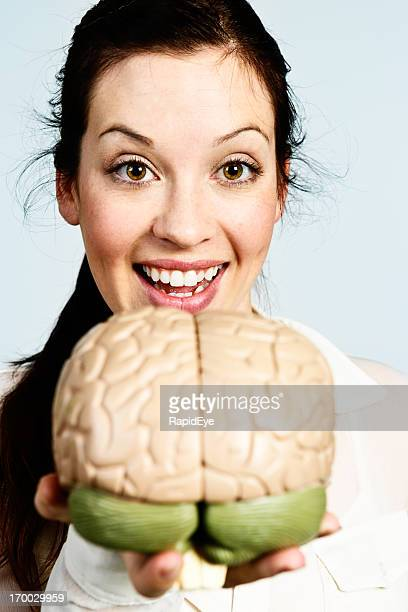 Happy brunette holds up anatomical model of human brain