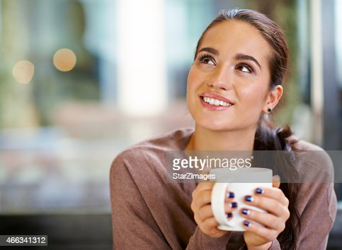 Happy brunette with mug in hands looking to the corner