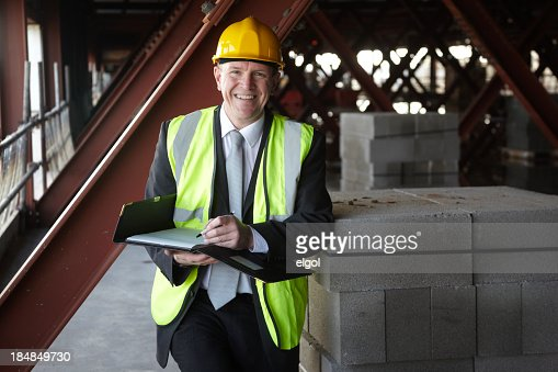 Happy building executive on construction site