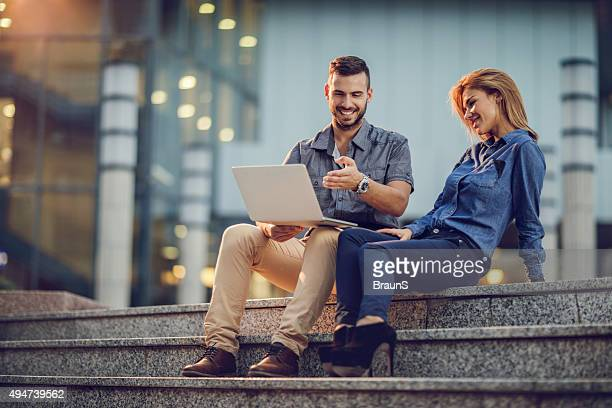 Happy business colleagues working on laptop while relaxing on staircase.