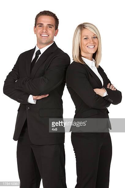 Heureux couple d'affaires debout avec les bras croisés
