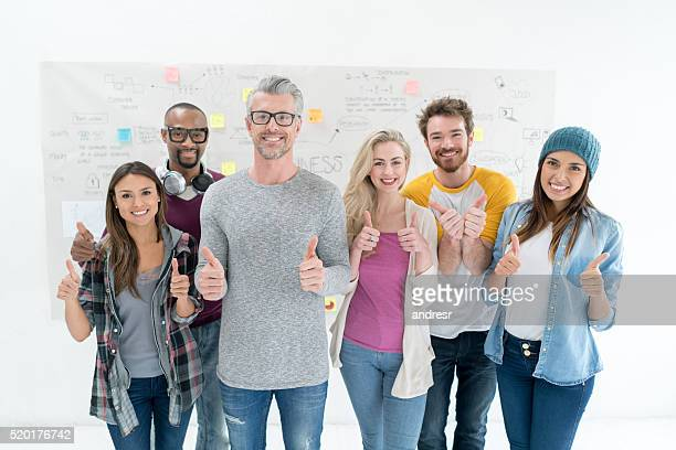 Happy business group with thumbs up