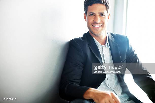 Happy business man leaning against the wall