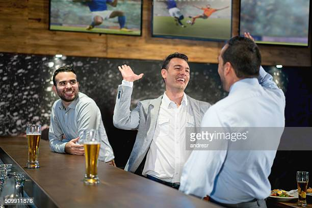 Happy business men having drinks at the bar