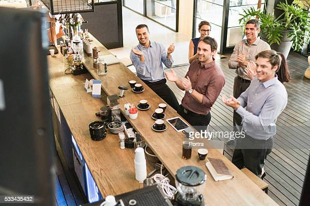 Happy business people applauding at coffee counter