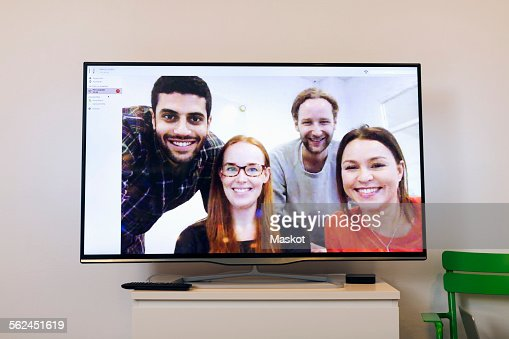 Happy business people on screen in video conference room at creative office