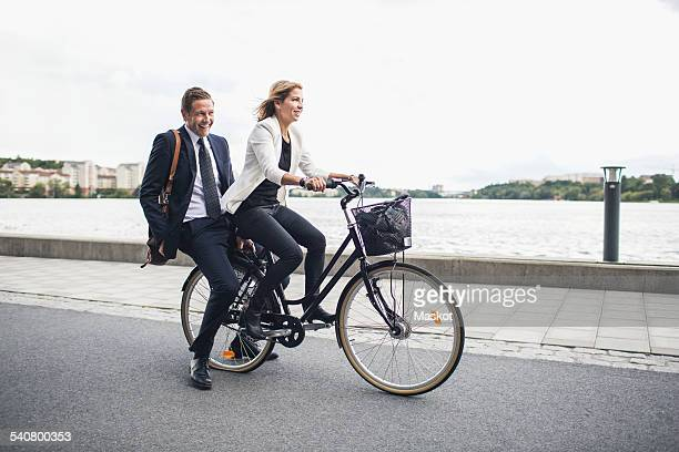 Happy business people riding on bicycle in city street