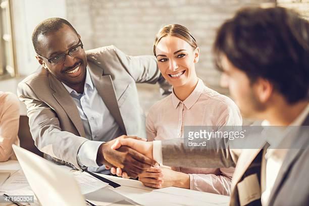 Feliz hombres de negocios estrechándose las manos en la oficina.