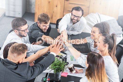 Happy business people team giving high five in office. : Stock Photo