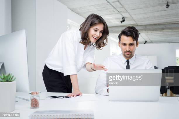 Happy business people working together on laptop