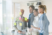 Smiling businessmen and businesswomen looking at sticky notes in board room. Creative business team looking at adhesive notes in office. Successful business teamwork discussing over sticky notes.