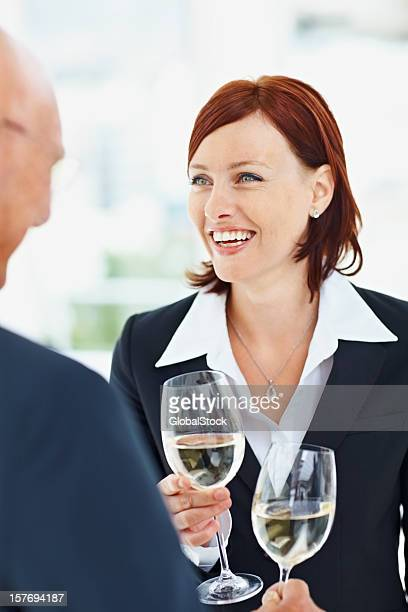 Happy business woman and man holding flute with champagne